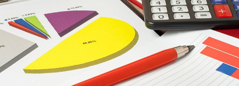 Grafieken, rekenmachine en pen op houten bureau tafel. Financiële en zakelijke concept, Prinsjesdag, Miljoenennota